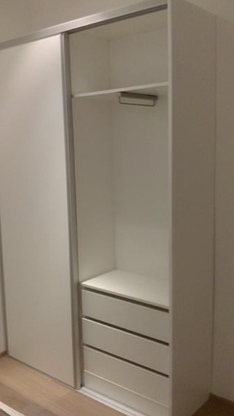 Armario con puertas correderas lacadas en blanco con perfil de aluminio.