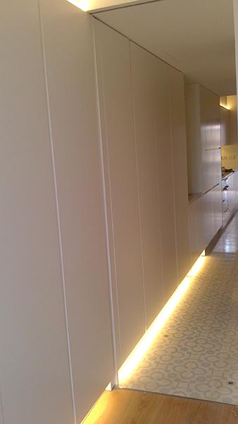 Armario pasillo con puertas practicables lacadas en blanco con uñero. Instalación en Paralelo de Barcelona