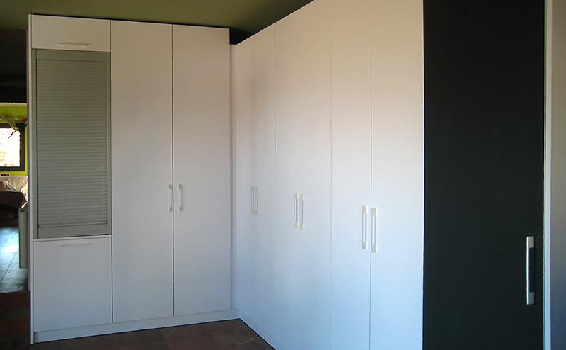 Armario con puertas practicables combinadas en fórmica blanca y fórmica pizarra con un módulo de persiana enrollable. Instalación en Cellers