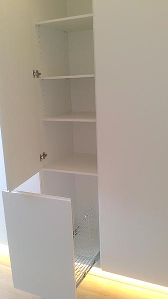 Mueble columna a medida lacado blanco con uñero. Tolva extraíble