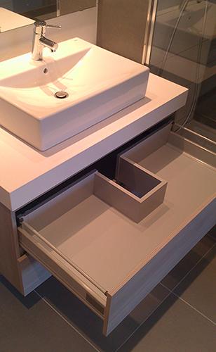 Mueble de baño suspendido a medida en melamina imitación madera. Cajones con guía de extracción total con freno.