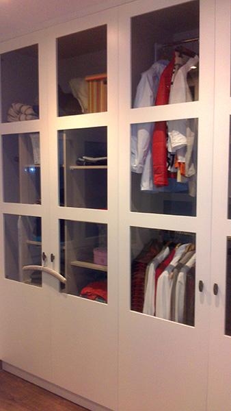 Armario ropero empotrado con puertas practicables con vitrinas con cristal transparente en rechapado teñido color blanco.