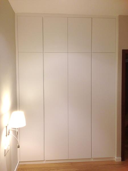 Armario ropero empotrado para dormitorio con puertas practicables lacadas en blanco con uñero.