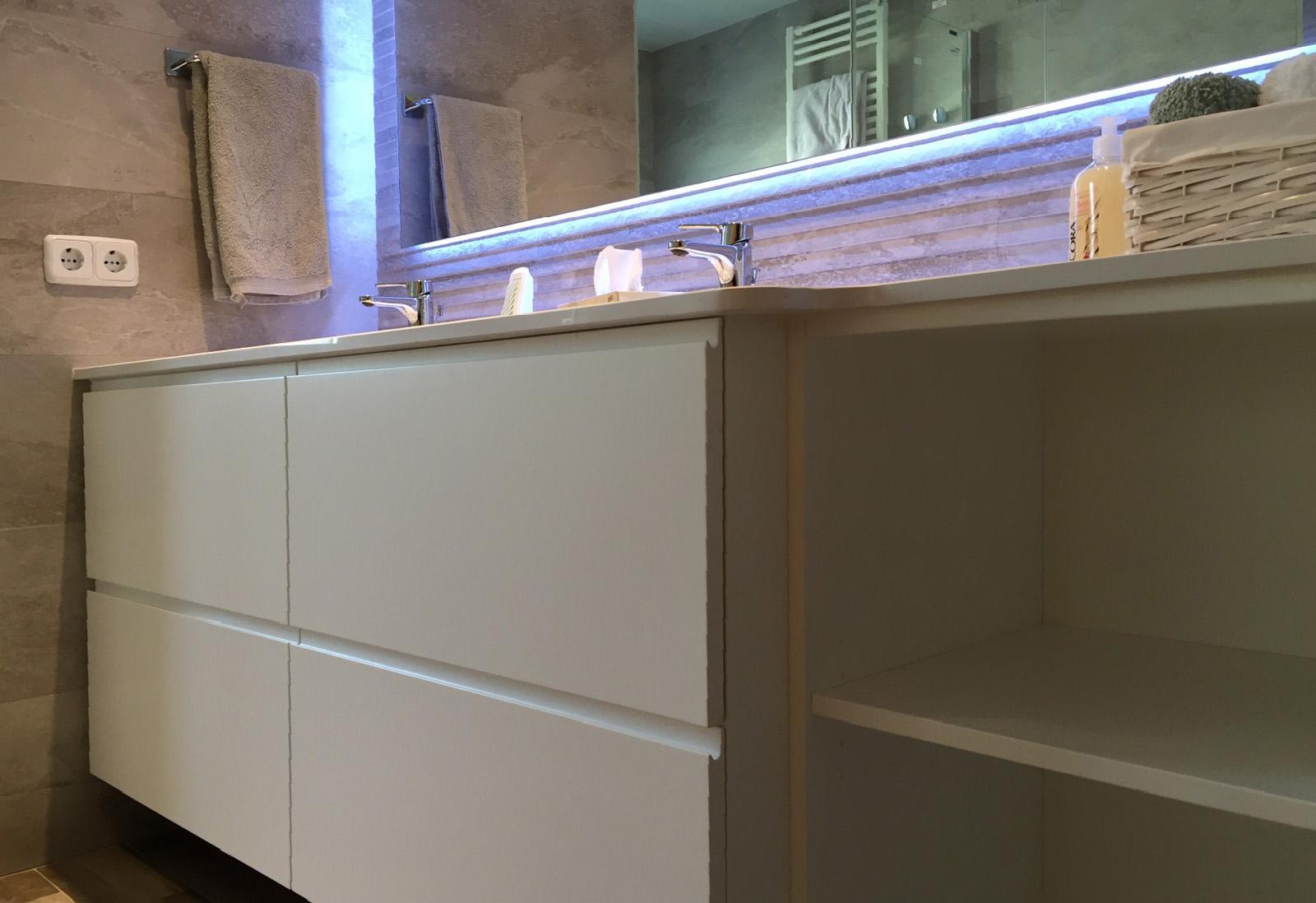 Mueble de baño a medida suspendido lacado blanco con uñero y cajones de extracción total con freno, con espejo retroiluminado.
