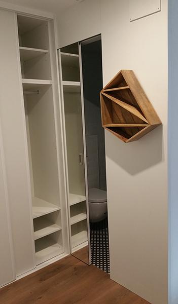Armario a medida en melamina blanca con puertas correderas con perfil de aluminio blanco y puerta de paso corredera con espejo.
