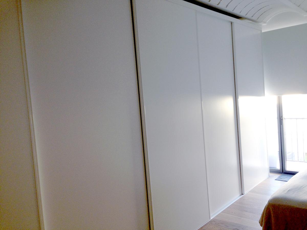 Armario de puertas correderas lacadas en blanco satinado con perfilería de aluminio